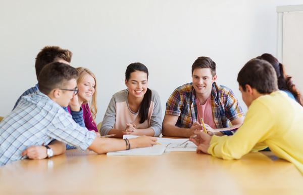 Gruppe junger Menschen sitzt um einen Tisch und diskutiert